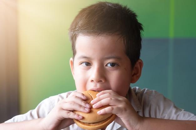 アジアの男の子の肖像画はハンバーガーを食べています。健康の概念 Premium写真