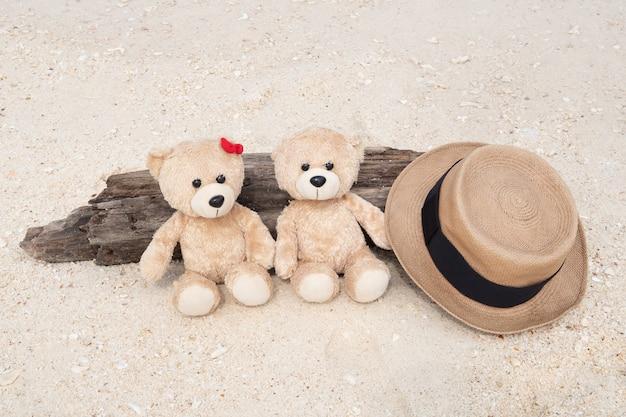 Два плюшевых медведя сидят на бревне с видом на море Premium Фотографии