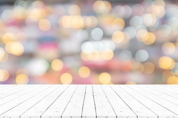 Деревянный стол перспективы пустой белый на верхней части над предпосылкой нерезкости, можно использовать насмешку вверх для дисплея продуктов монтажа или плана дизайна. Premium Фотографии