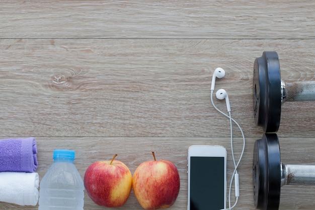 タオル、水、リンゴ、ダンベル、携帯電話のボトルとフィットネスコンセプト。上から見る Premium写真