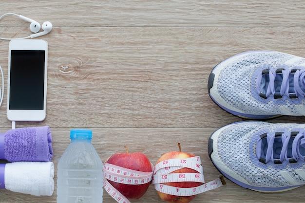 ランニングシューズ、タオル、水、リンゴ、測定テープ、携帯電話のボトルとフィットネスコンセプト上から見る Premium写真