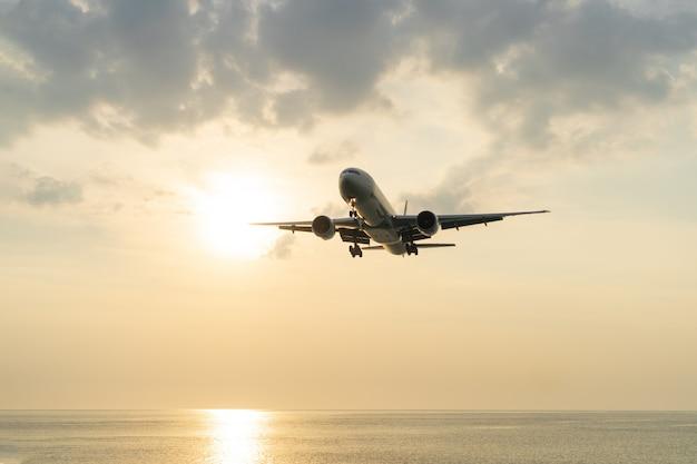 飛行機は日没で海の上に座っています。 Premium写真