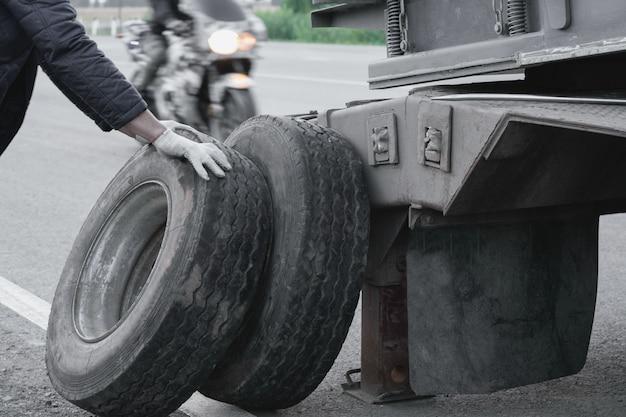 Грузовик с негабаритным грузом выезжает на дорогу. лопнуло колесо. Premium Фотографии