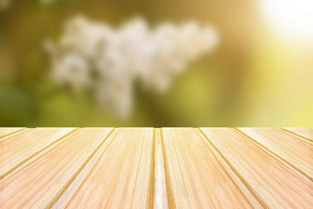 ぼやけた春の背景、花と公園のボケ味を持つ空の木製テーブル Premium写真