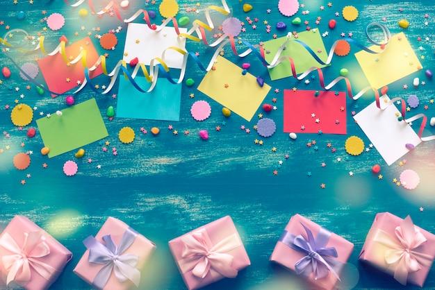 ホリデー色の紙吹雪の蛇行紙のギフトボックスのためのお祝いの明るい青色の背景の装飾 Premium写真