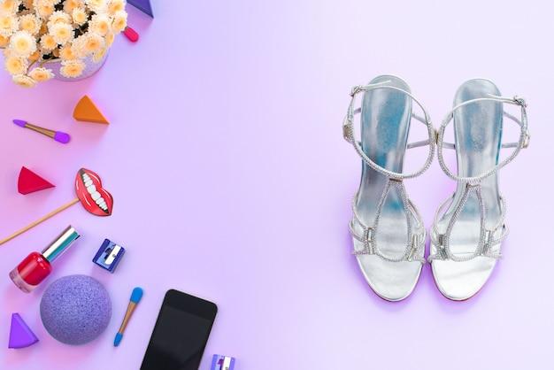 アクセサリー化粧品靴ガジェットモバイル花紫色の背景 Premium写真