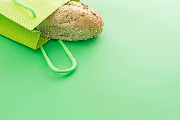 緑色の背景で買い物袋に焼きたてのパン。 Premium写真