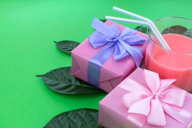 休日ポスターギフトボックスとミルクセーキのガラスは、明るい緑の背景。 Premium写真