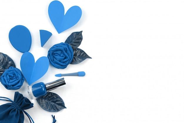 Предпосылка декоративной косметики в сини на белизне. концепция дня святого валентина композиция плоская лежащая губная помада цветок сердце лист лак для ногтей Premium Фотографии