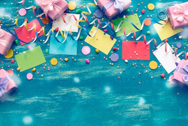 休日のためのお祝いの明るい青色の背景装飾色紙吹雪蛇紋岩紙ギフトボックス Premium写真