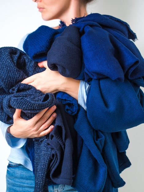 青い色のセーターの柔らかい暖かい編み物服の山を保持している女性の手。 Premium写真