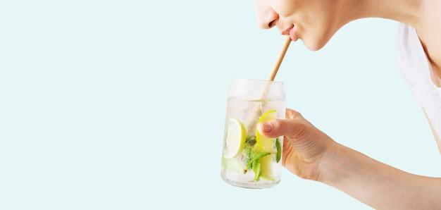 トロピカルモヒートカクテルのグラスを持って、ストローでそれを飲みながら女性の手のクローズアップ Premium写真