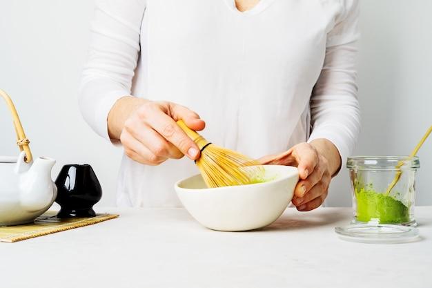 白人女性が竹茶碗で泡立て器で泡立てて日本の緑抹茶を準備 Premium写真