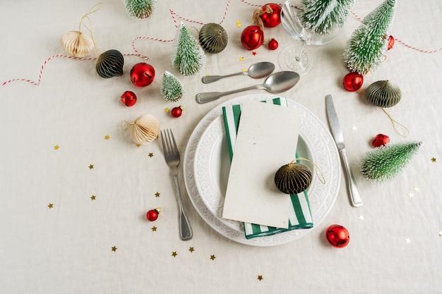 Красивая сервировка на сером фоне с белыми тарелками, стеклом, столовыми приборами и елочными украшениями Premium Фотографии