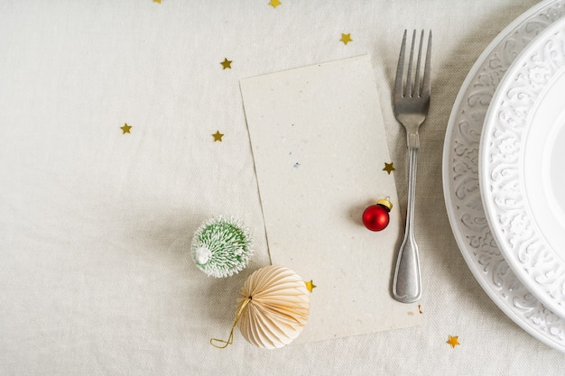 Красивая рождественская сервировка с местом для меню над белыми тарелками с серебряными столовыми приборами на фоне льняной скатерти Premium Фотографии