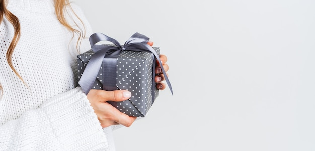 弓でギフトボックスを保持しているウールの白いセーターの女性。クリスマスのお祝いレイアウト。新年のモックアップ。幅広のバナー。 Premium写真