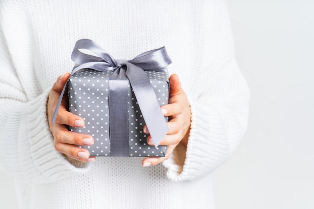 弓でギフトボックスを保持しているウールの白いセーターの女性。クリスマスのお祝いレイアウト。新年のモックアップ。 Premium写真