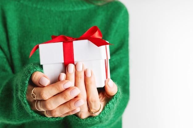 弓で現在の赤いギフトボックスを保持しているウールの緑のセーターの女性。クリスマスのお祝いレイアウト。新年のモックアップ。幅広のバナー。 Premium写真