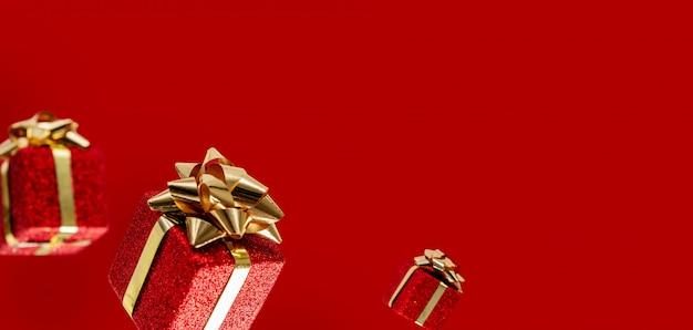 Подарки летят в воздухе на красном фоне. распродажа. концепция левитации. рождественский макет с копией пространства. Premium Фотографии