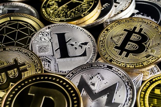 Много криптовалютных монет лежат на темной поверхности Premium Фотографии