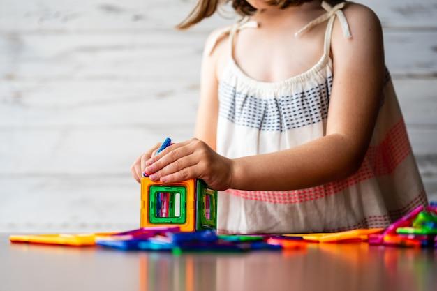 Портрет красивой вдумчивой маленькой девочки, играющей красочный магнит пластиковых блоков, Premium Фотографии
