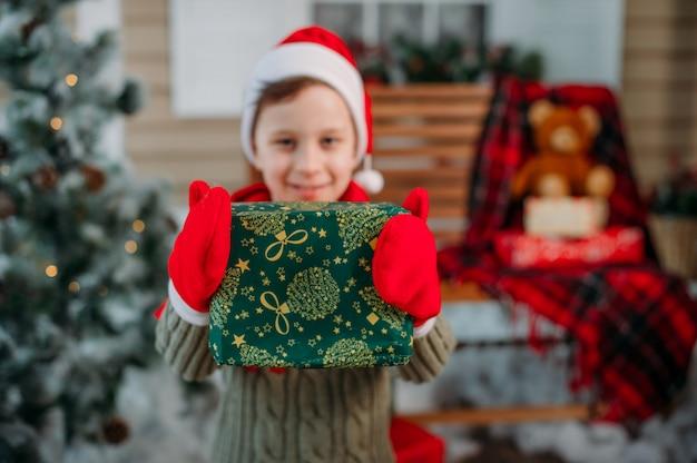 Счастливый мальчик с подарками в рождественские украшения Premium Фотографии