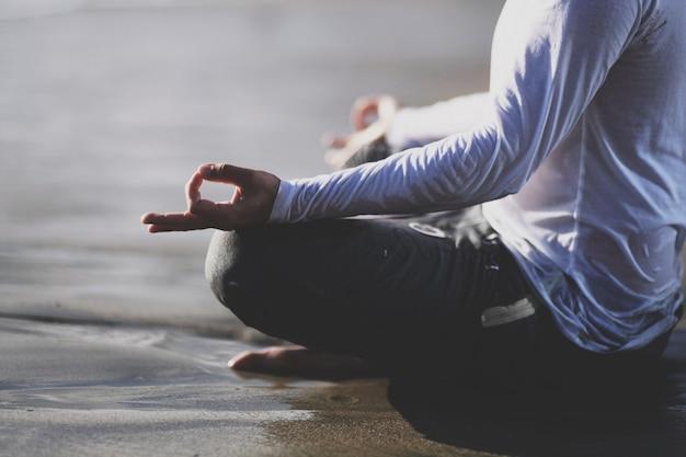 Йога практики молодого человека на пляже на заходе солнца. Premium Фотографии