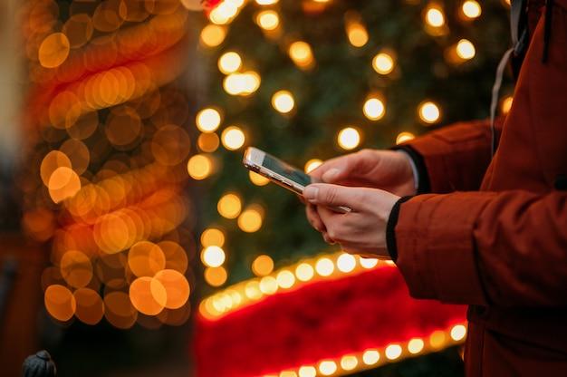 照らされたクリスマスツリーに対してスマートフォンを使用している人の中央部。 Premium写真
