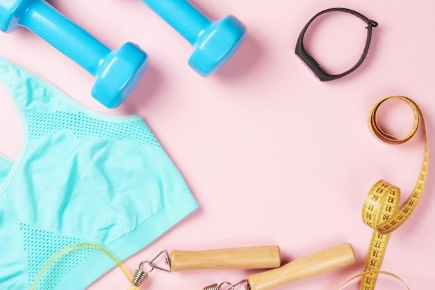 スポーツブラ、ダンベル、測定テープ、縄跳び、ピンクの背景のフィットネストラッカー Premium写真