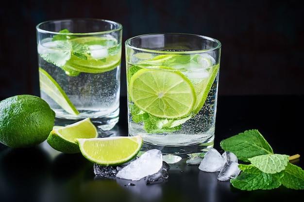 夏の飲み物レモネードモヒート、ライム、ミント、氷と黒の背景 Premium写真
