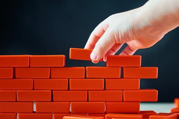 手は壁に最後のレンガを置きます。建設および建築の概念 Premium写真