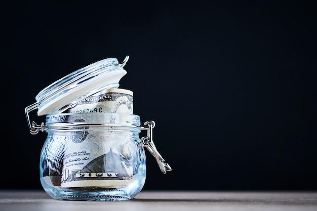 Счеты доллара сша в стеклянной банке с копией пространства. экономия денег и инвестиционная концепция Premium Фотографии