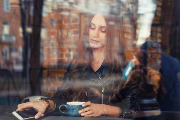 魅力的な若い女性がカフェで携帯電話を使用して Premium写真