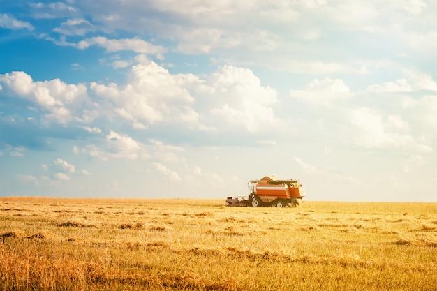 夏の日のフィールドで働く収穫機 Premium写真