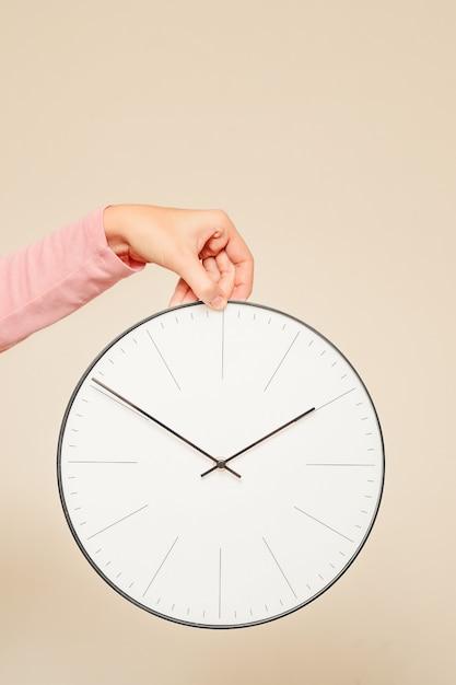 女性の手が白い背景の上の壁時計を保持します。 Premium写真