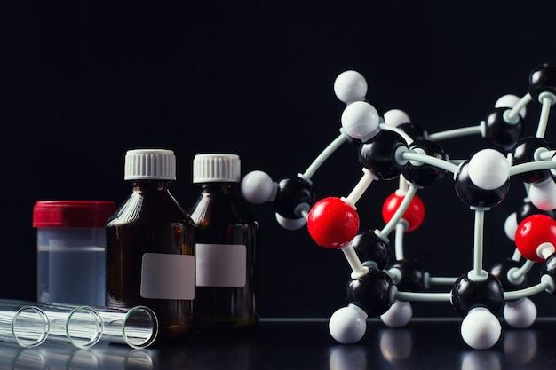 Молекулярная формула и лабораторное оборудование на темном фоне крупным планом. Premium Фотографии