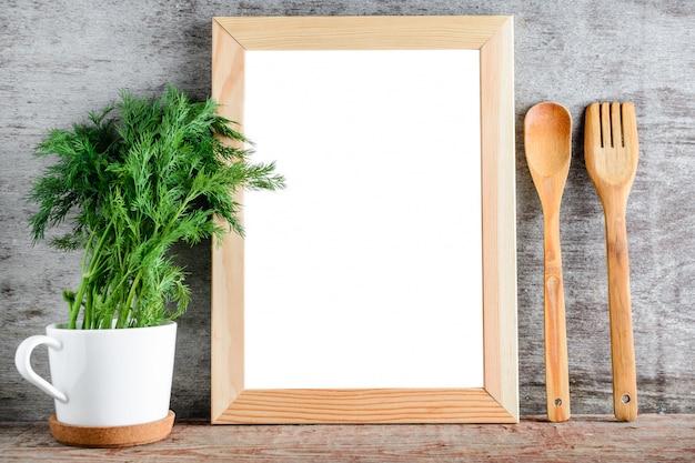 灰色の壁に空の木枠とキッチンアクセサリー。 Premium写真