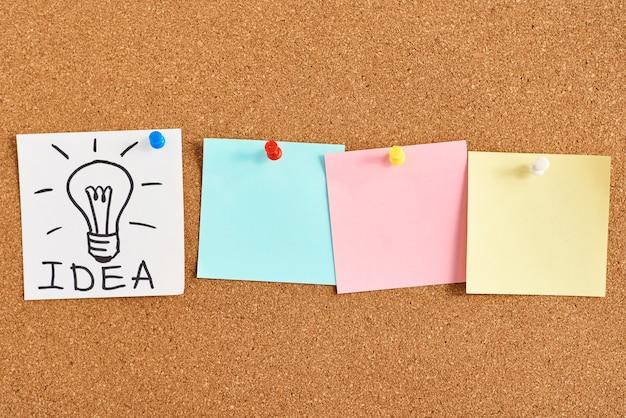 単語のアイデアとコルク板に色付きの白紙のメモと塗られた電球 Premium写真