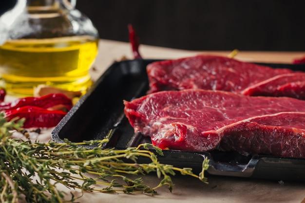 新鮮な生のスライス肉ビーフステーキとフライパン、クローズアップ Premium写真