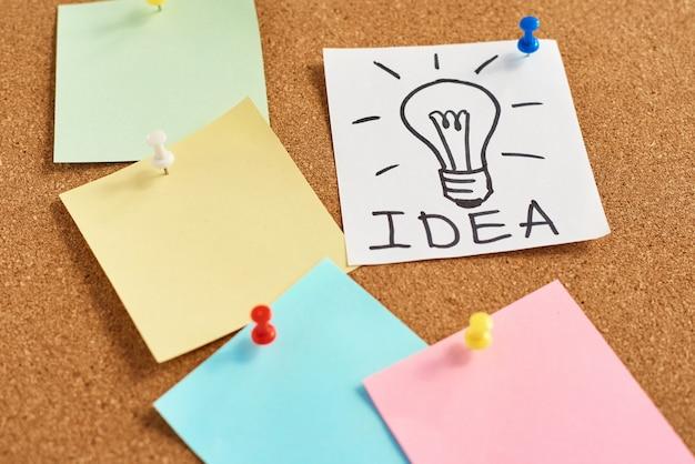 単語のアイデアとコルク板に色付きの白紙のメモと塗装電球 Premium写真