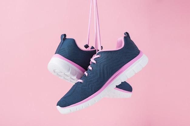 Женские кроссовки для запуска на розовом фоне. модная стильная спортивная обувь, крупный план Premium Фотографии