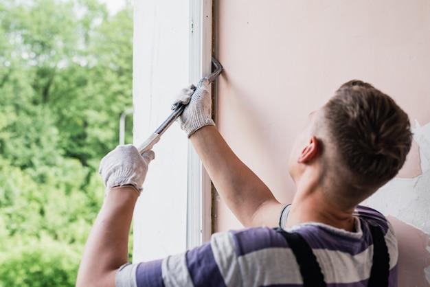Рабочий мужского пола, ремонт окна в доме, крупным планом Premium Фотографии