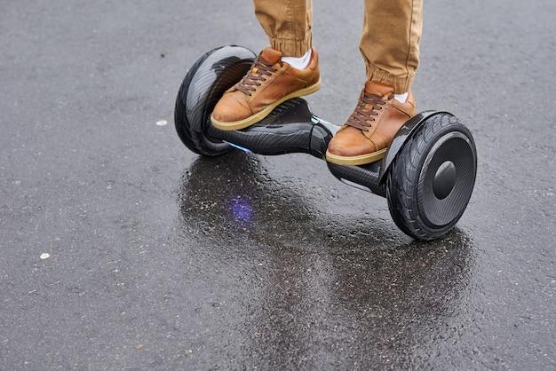 ホバーボードアスファルト道路、屋外の電気スクーターに足を使用している人のクローズアップ Premium写真