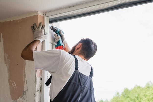Процесс человека с помощью отвертки. работник делает установку окна Premium Фотографии