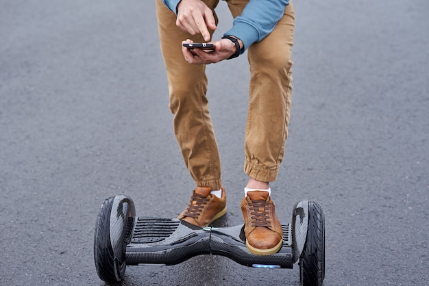 電気ジャイロスクーターのアプリケーションを持つ手にスマートフォン。男は屋外でホバーボードを使用します Premium写真