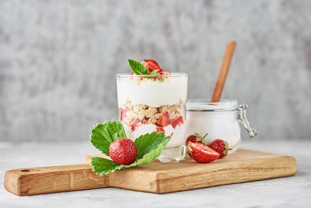 ガラス、新鮮な果実、まな板の上の砂糖の瓶にイチゴとグラノーラまたはヨーグルト Premium写真