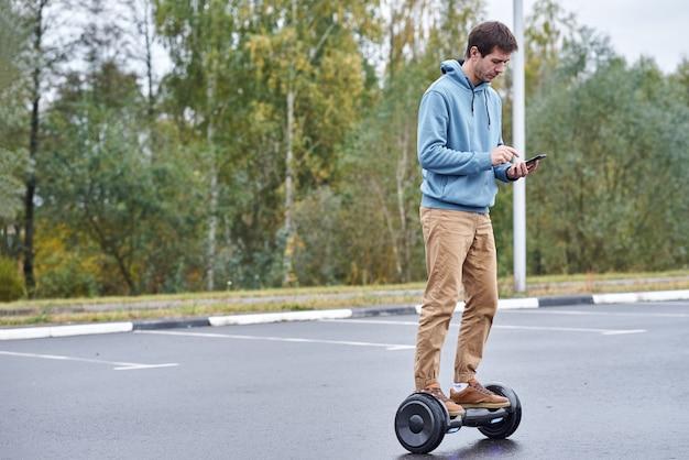 Человек верхом на ховерборде и с помощью смартфона на открытом воздухе Premium Фотографии