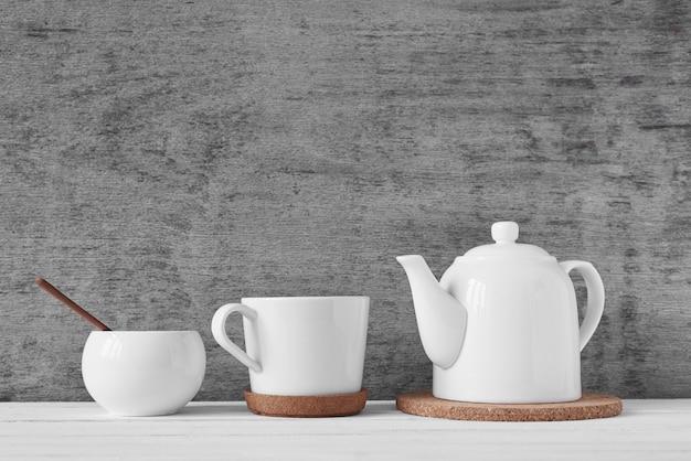 Чашка чая, чайник, сахарница Premium Фотографии