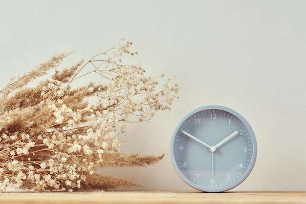 目覚まし時計と木製テーブルの上の乾燥植物と自家製の花瓶 Premium写真