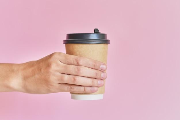 コーヒーの紙コップを持っている女性の手はピンクの背景に奪う Premium写真